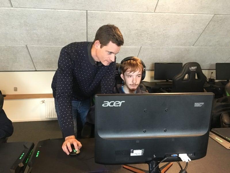 Lærer med elev ved computer